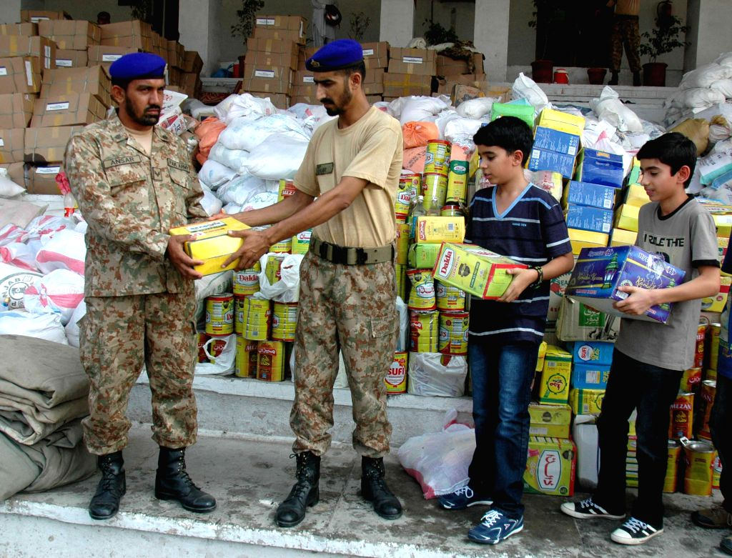 Pakistan army soldiers store relief goods for the internally displaced civilians, fleeing from the military operation against militants of North Waziristan region, ..