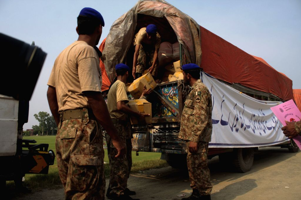 Pakistani soldiers load relief supplies into a truck for internally displaced civilians, fleeing from the military operation against militants in North Waziristan, ..