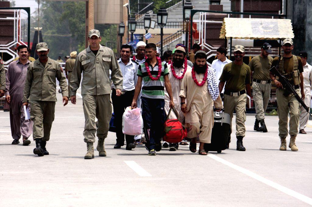 Pakistani rangers escort released Pakistani prisoners at the Wagah border in eastern Pakistan's Lahore on July 4, 2014. India on Friday released nine Pakistani ...