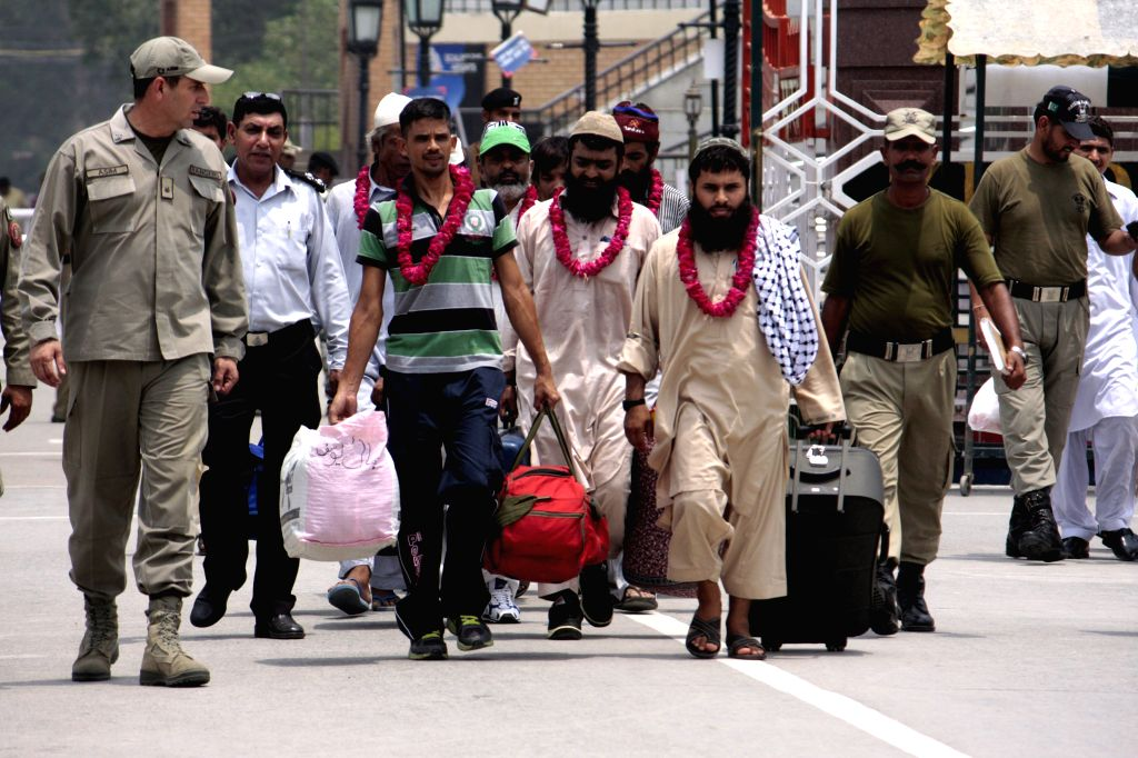 Released Pakistani prisoners walk across the Wagah border in Lahore, east Pakistan, on July 4, 2014. India on Friday released nine Pakistani prisoners (four civil ...