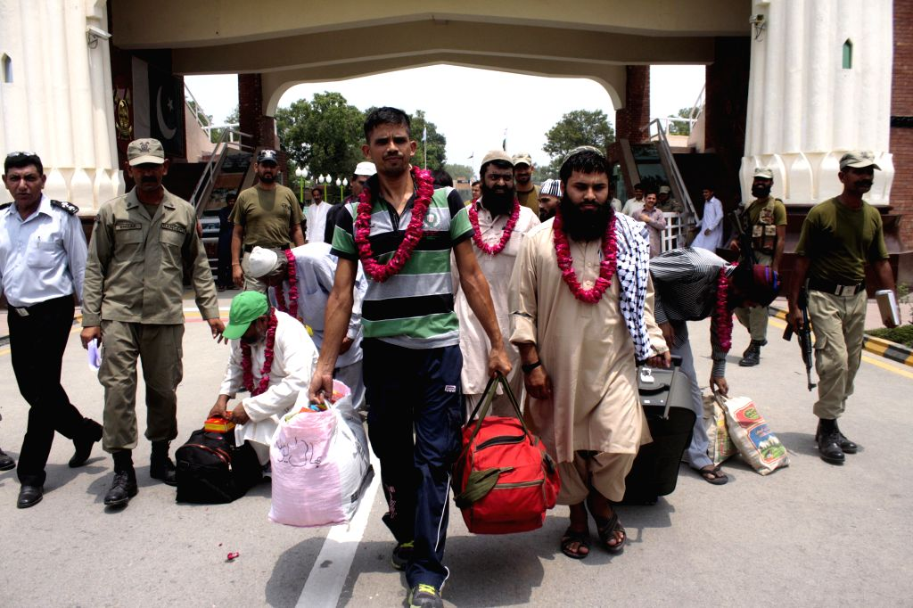 Released Pakistani prisoners walk across the Wagah border in eastern Pakistan's Lahore on July 4, 2014. India on Friday released nine Pakistani prisoners (four civil .