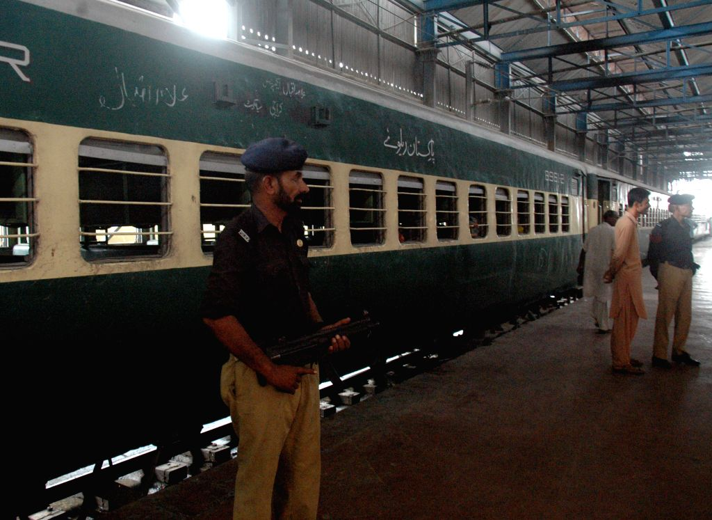 A policeman stands guard near a train at a railway station due to security high alert in eastern Pakistan's Lahore, July 9, 2014. Security tightened in Lahore railway