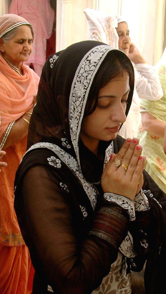 An Indian Sikh female devotee prays at the Gurdwara Dhara Sahib in Lahore, east Pakistan, on June 16, 2014.