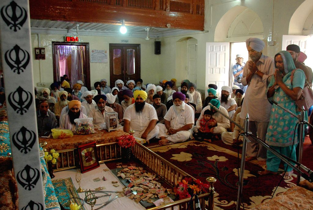 Indian Sikh devotees pray at the Gurdwara Dhara Sahib in Lahore, east Pakistan, on June 16, 2014.