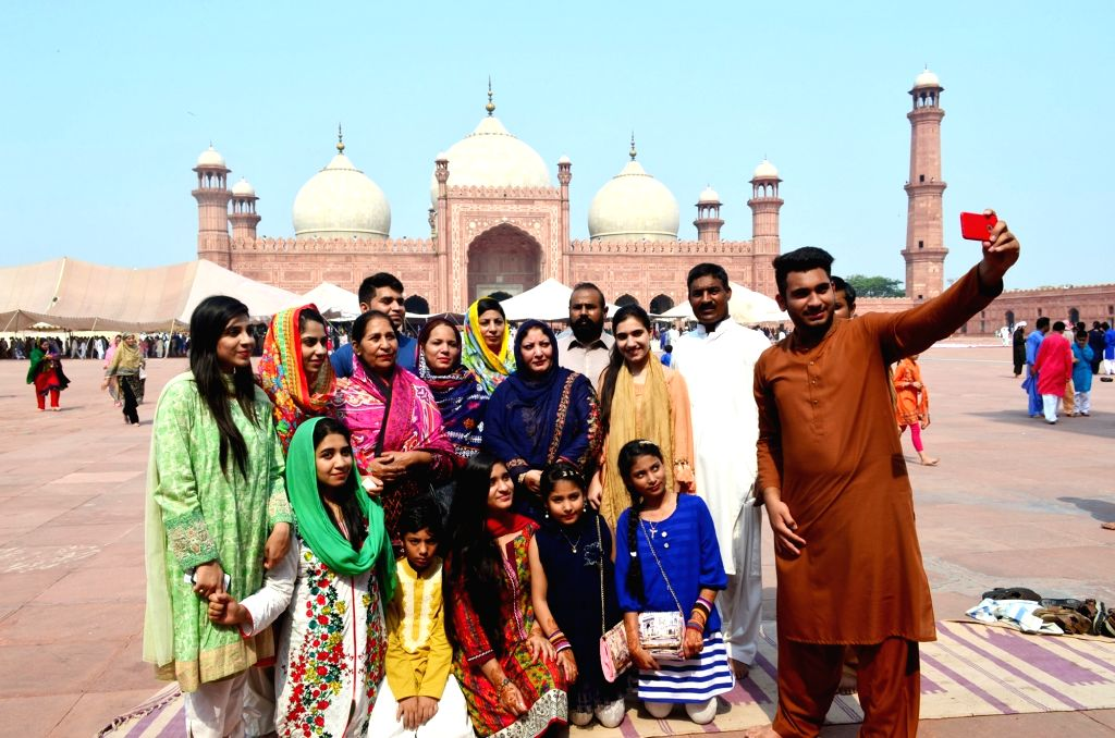 LAHORE, June 26, 2017 - Muslims take a selfie after offering Eid al-Fitr prayers marking the end of the holy fasting month of Ramadan, at Badshahi mosque in eastern Pakistan's Lahore, on June 26, ...