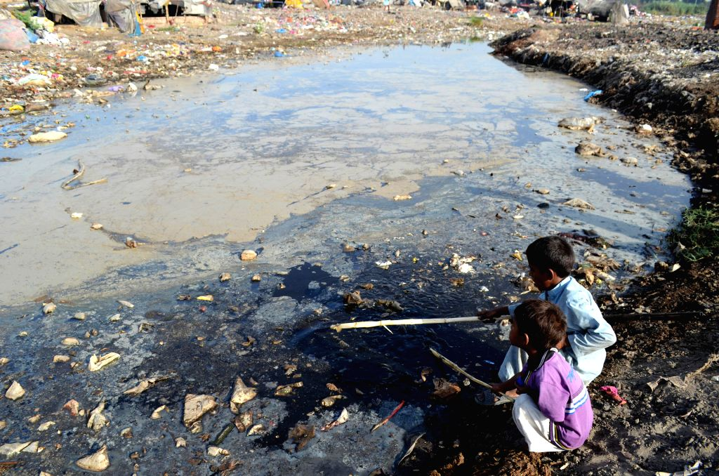 LAHORE, June 4, 2016 - Pakistani boys play beside a dirty water canal on the outskirts of eastern Pakistan's Lahore, June 4, 2016. World Environment Day will be celebrated on June 5 this year and is ...