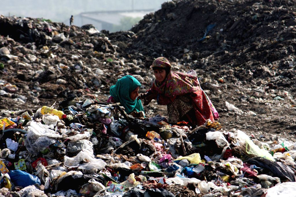 LAHORE, June 4, 2016 - Pakistani girls search for recyclable items from a garbage dump site on the outskirts of eastern Pakistan's Lahore, June 4, 2016. World Environment Day will be celebrated on ...