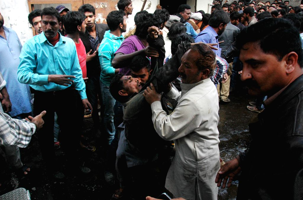 People carry an injured man from the blast site in eastern Pakistan's Lahore on March 15, 2015. At least 10 people were killed and 48 others wounded when two ...
