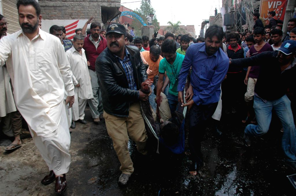 People remove a body from the blast site in eastern Pakistan's Lahore on March 15, 2015. At least 10 people were killed and 48 others wounded when two suicide ...
