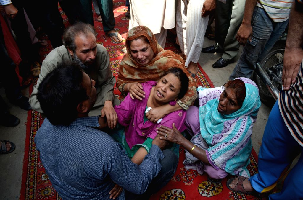 People mourn over the death of their relatives in the collapse accident in eastern Pakistan's Lahore, March 24, 2015. At least three people were killed as a ...