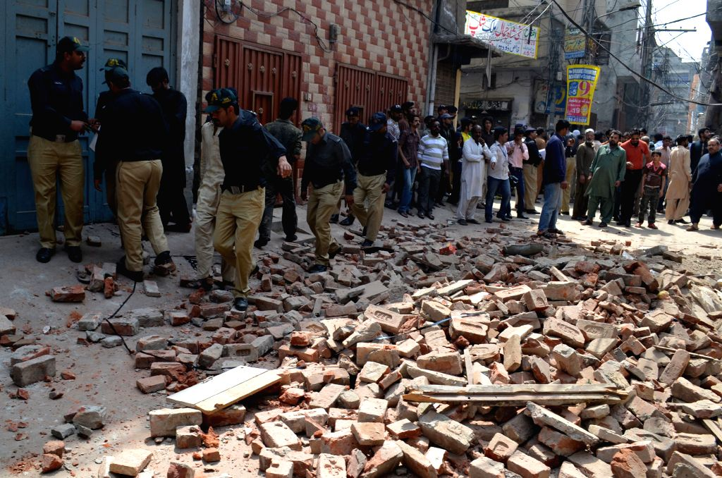 Policemen inspect the accident site in eastern Pakistan's Lahore, March 24, 2015. At least three people were killed as a residential building in downtown Lahore ...
