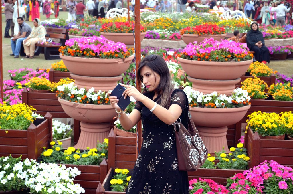 A woman takes photos at a flower show in eastern Pakistan's Lahore, on March 27, 2015. Flowers are in full blossoms as temperature rises in Pakistan. (Xinhua/Jamil ...