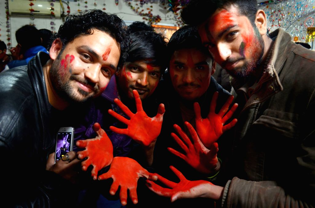 Pakistani Hindus with colored powder on their faces celebrate Holi festival, also known as the festival of colors, in eastern Pakistan's Lahore on March 5, 2015. ...