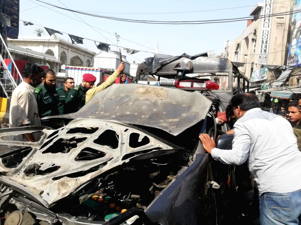 LAHORE, May 8, 2019 (Xinhua) -- People inspect a damaged police vehicle at the blast site in Pakistan's eastern city of Lahore on May 8, 2019. At least eight people, including five policemen, were killed and 25 others injured on Wednesday in the suic