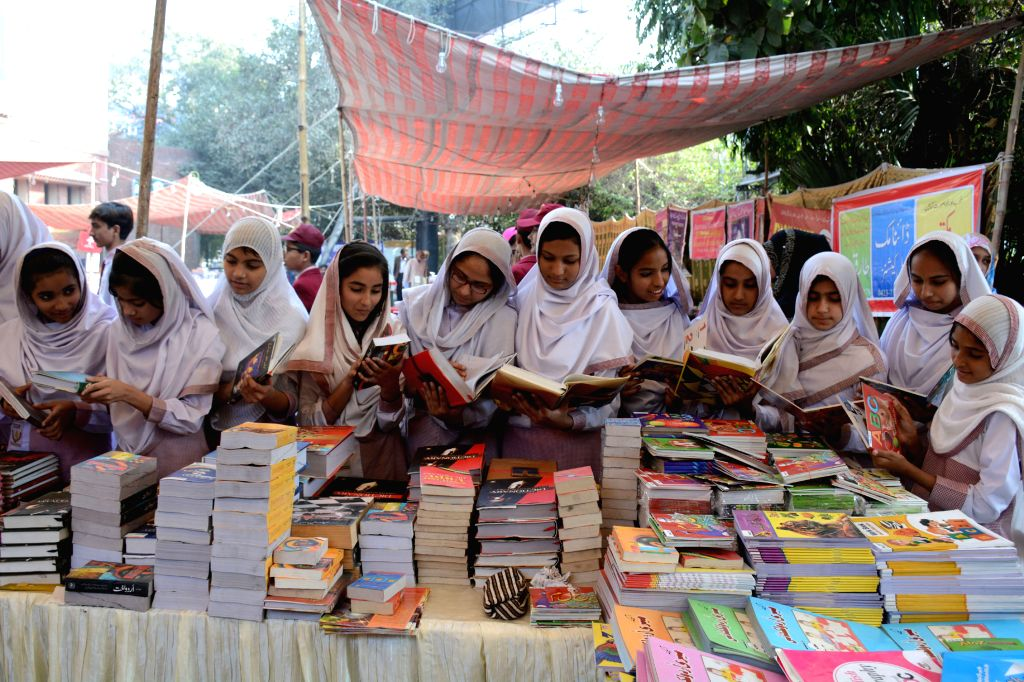 LAHORE, Nov. 19, 2016 - Girls read books at a stall on the eve of the Universal Children's Day in eastern Pakistan's Lahore, Nov. 19, 2016. Universal Children's Day, which falls on Nov. 20 every ...