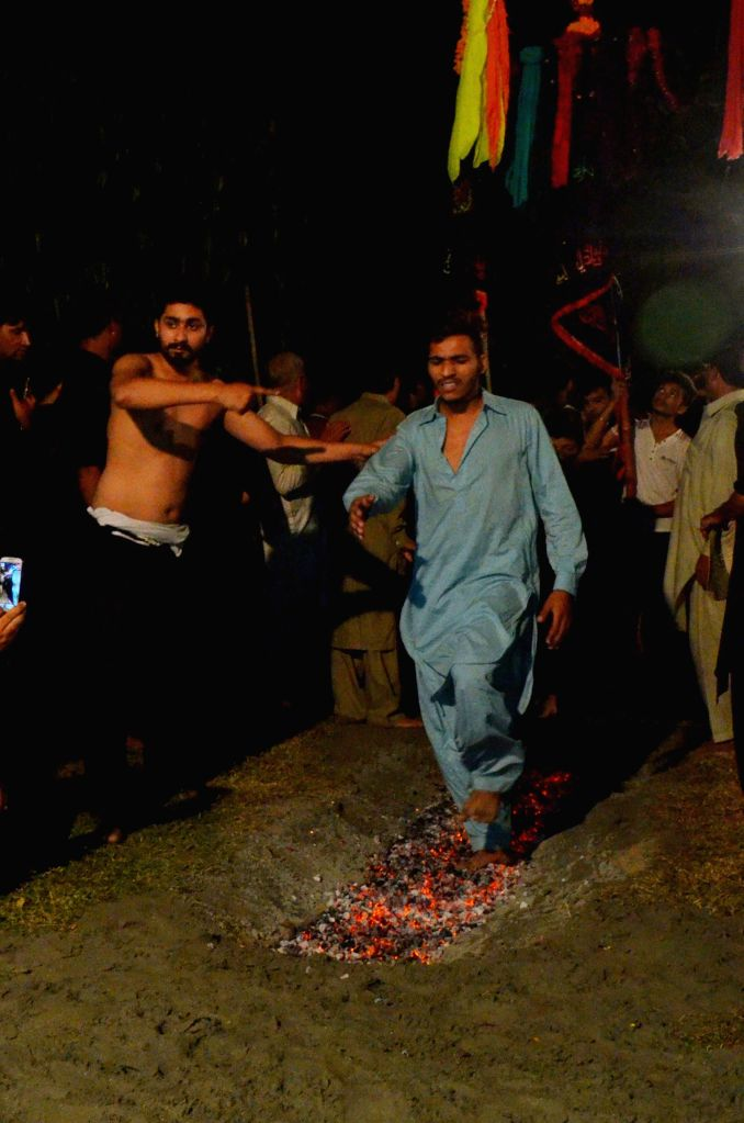 LAHORE, Oct. 10, 2016 - A Pakistani Shiite Muslim walks on hot coals during a Muharram procession in eastern Pakistan's Lahore, Oct. 10, 2016. The Islamic month of Muharram marks the martyrdom of ...