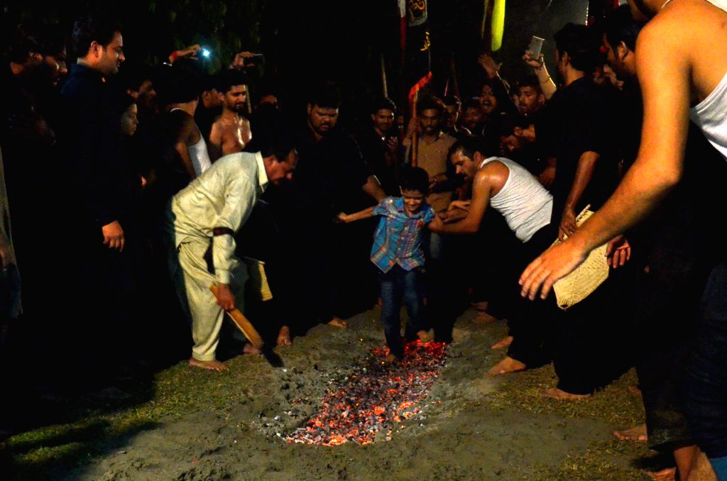 LAHORE, Oct. 10, 2016 - A Pakistani Shiite Muslim boy walks on hot coals during a Muharram procession in eastern Pakistan's Lahore, Oct. 10, 2016. The Islamic month of Muharram marks the martyrdom of ...