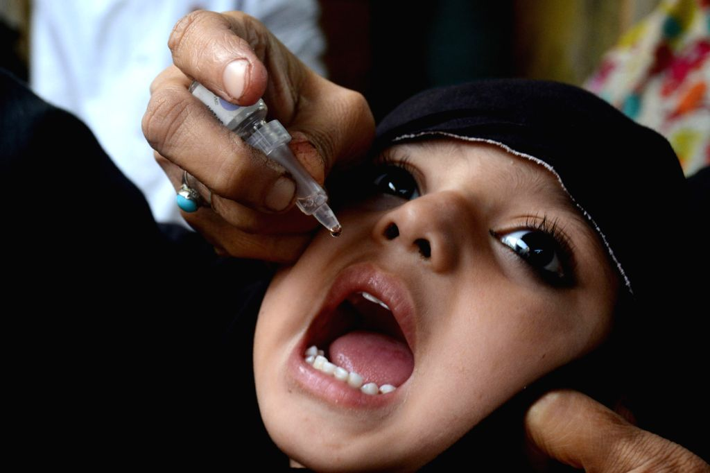 LAHORE, Oct. 24, 2016 - A Pakistani health worker gives a polio vaccine to a child on World Polio Day in eastern Pakistan's Lahore, Oct. 24, 2016. The World Polio Day was observed across the globe on ...