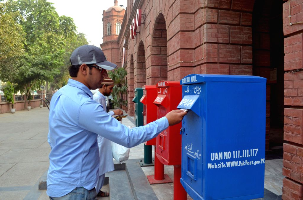 LAHORE, Oct. 8, 2016 - A man puts a letter into a mailbox at a post office on the eve of World Post Day in eastern Pakistan's Lahore, Oct. 8, 2016. World Post Day is celebrated each year on Oct. 9, ...