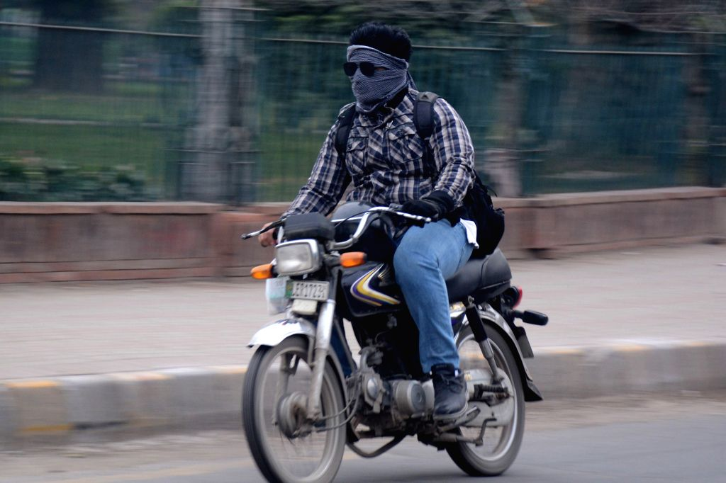 LAHORE (PAKISTAN), Nov. 15, 2019 A man with his face covered rides a motorbike amid heavy smog in Lahore, eastern Pakistan, on Nov. 15, 2019. The air quality in Lahore and adjoining ...