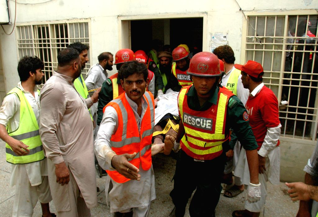 Rescuers remove a body at the collapsed mosque site in eastern Pakistan's Lahore on Sept. 9, 2014. At least 24 people were killed and several others trapped when ...