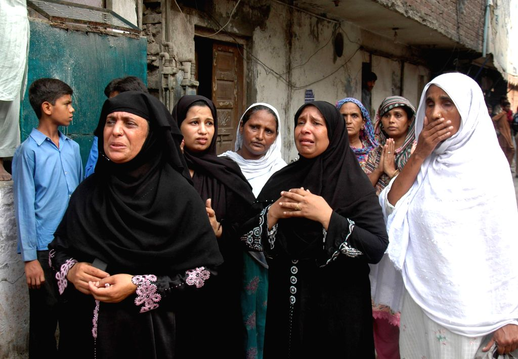 Women react at the collapsed mosque site in eastern Pakistan`s Lahore on Sept. 9, 2014. At least 24 people were killed and several others trapped when roof of a ...