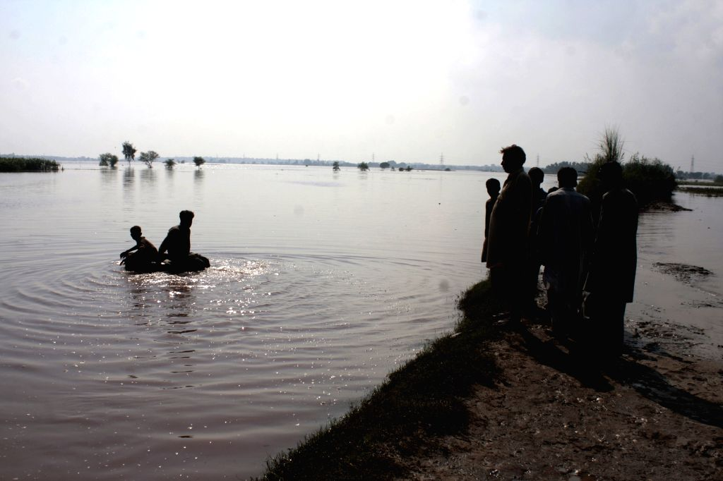 Pakistanis stand on a high land in the flood-hit village of Chung near Lahore, eastern Pakistan, on Sept. 11, 2014. Pakistani troops used helicopters and boats to ..