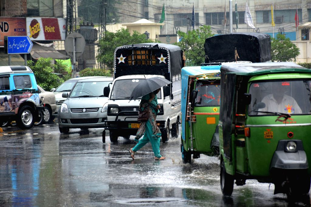 LAHORE, Sept. 20, 2016 - A woman uses umbrella as she crosses a road with heavy traffic during heavy rain in eastern Pakistan's Lahore, Sept. 20, 2016.
