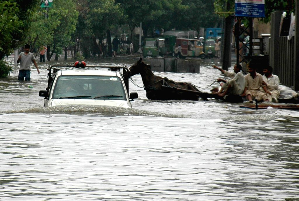A vehicle and a horse cart move on a flooded street after heavy monsoon rains in eastern Pakistan's Lahore on Sept. 5, 2014. At least 72 people were killed and over .