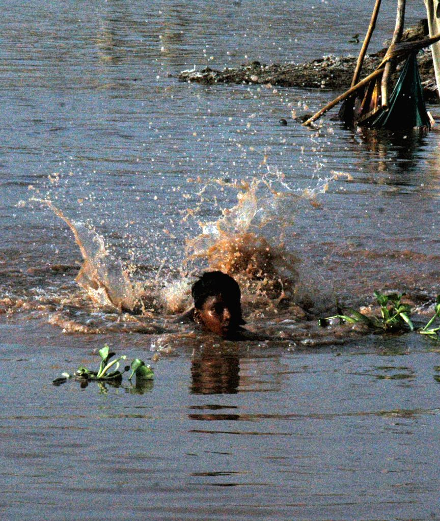 A Pakistani boy swims in the flooded Ravi River in east Pakistan's Lahore, Sept. 8, 2014. At least 165 people were killed and over 200 others injured when torrential