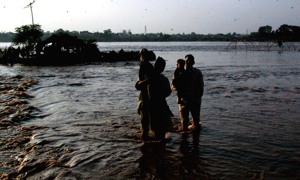Pakistani people wade through on the high land of the flooded Ravi River in eastern Pakistan's Lahore, Sept. 8, 2014. At least 165 people were killed and over 200 ...