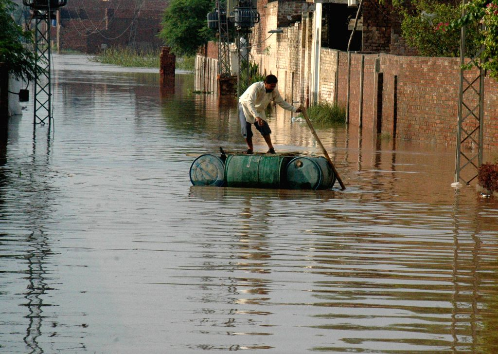 A man wades through flooded water from flood-hit area near east Pakistan's Lahore, Sept. 9, 2014. At least 203 people have been killed and hundreds others injured in