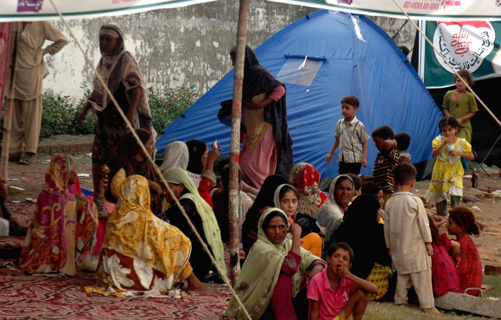 Pakistani flood-effected people sit at a makeshift tent as they flee from flood-hit area near east Pakistan's Lahore, Sept. 9, 2014. At least 203 people have been ...
