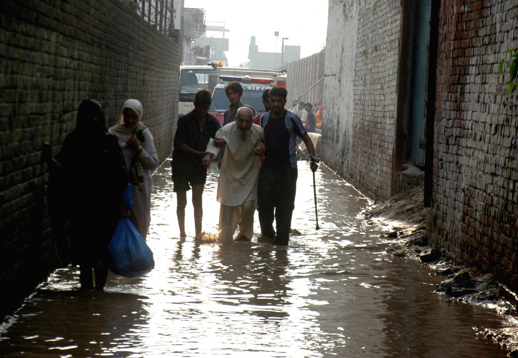 Pakistani volunteers help a man in flood-hit area near east Pakistan's Lahore, Sept. 9, 2014. At least 203 people have been killed and hundreds others injured in ...