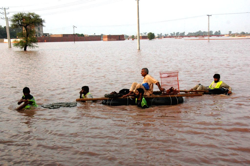 Pakistani volunteers rescue a man from flood-hit area near east Pakistan's Lahore, Sept. 9, 2014. At least 203 people have been killed and hundreds others injured in