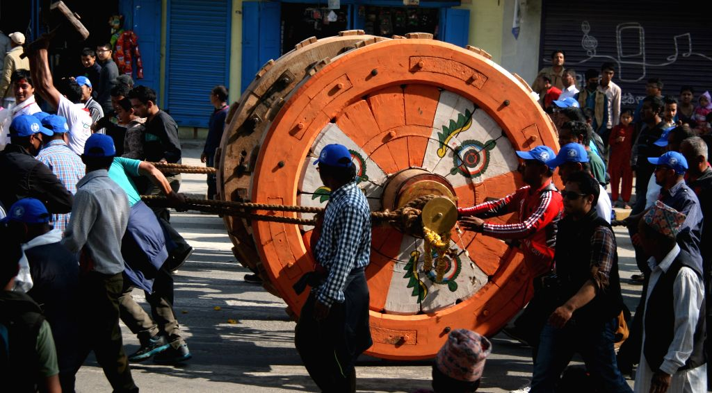 Poeple pull newly built wheels of Rato Machhendranath chariot during the preparation of the upcoming Rato Machhendranath Chariot festival in Lalitpur, Nepal, ...
