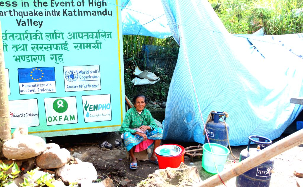 A woman sits near a makeshift tent after earthquake in Lalitpur, Nepal, April 29, 2015. The 7.9-magnitude quake hit Nepal at midday on Saturday. (Xinhua/Sunil ...