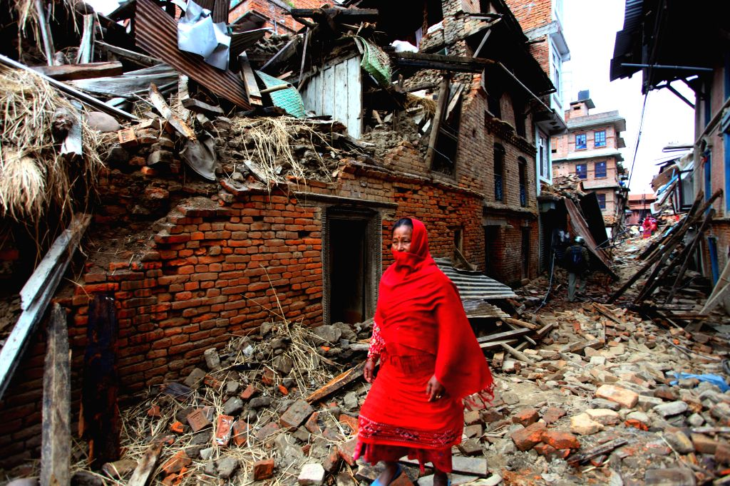 A woman walks past the debris after earthquake in Lalitpur, Nepal, April 29, 2015. The 7.9-magnitude quake hit Nepal at midday on Saturday. The death toll from ... - Sunil Sharma