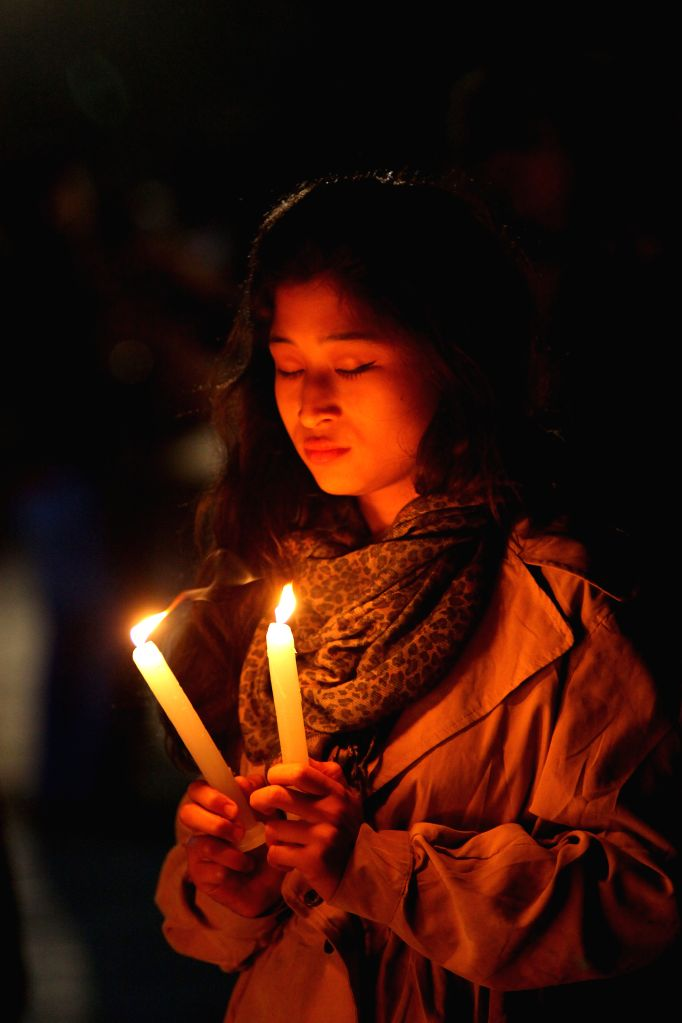 LALITPUR, Dec. 25, 2016 - A woman hold candles as she prays on Christmas Eve at a church in Lalitpur, Nepal, Dec. 24, 2016.