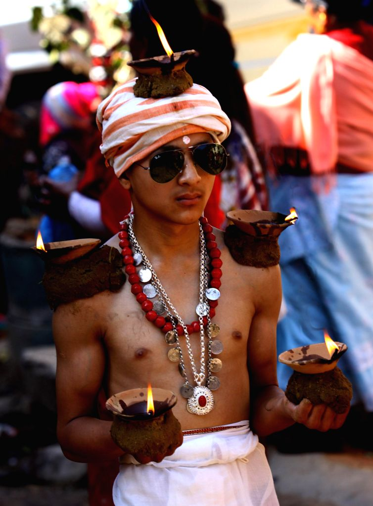 A Nepalese Hindu devotee carries oil lamps on his head and shoulders during the Madhav Narayan festival celebration in Thecho, Lalitpur, Nepal, Jan. 31, 2015. ...