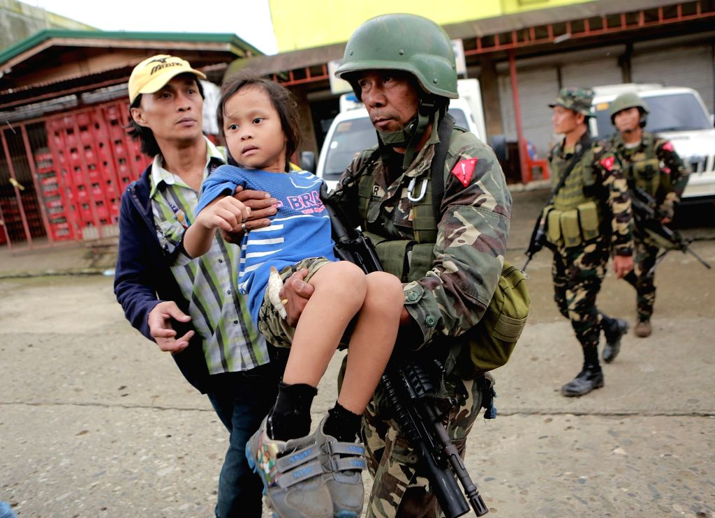 LANAO DEL SUR, May 31, 2017 - A soldier carries a child as they help trapped residents during a rescue operation in Lanao Del Sur Province, the Philippines, May 31, 2017. Government troops rescued 20 ...
