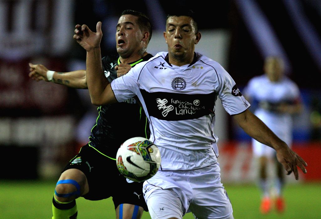 Lanus' Facundo Monteseirin (R) vies with Santos' Mauro Cejas during the first leg of the eight-finals of the 2014 Libertadores Cup at Ciudad de Lanus Stadium in ...