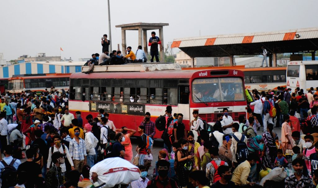 Large numbers of migrants at Kaushambi bus stand to board buses for their native place , after lockdown announcement in National Capital in the wake of rising Covid-19 cases, in New Delhi, Monday, ...