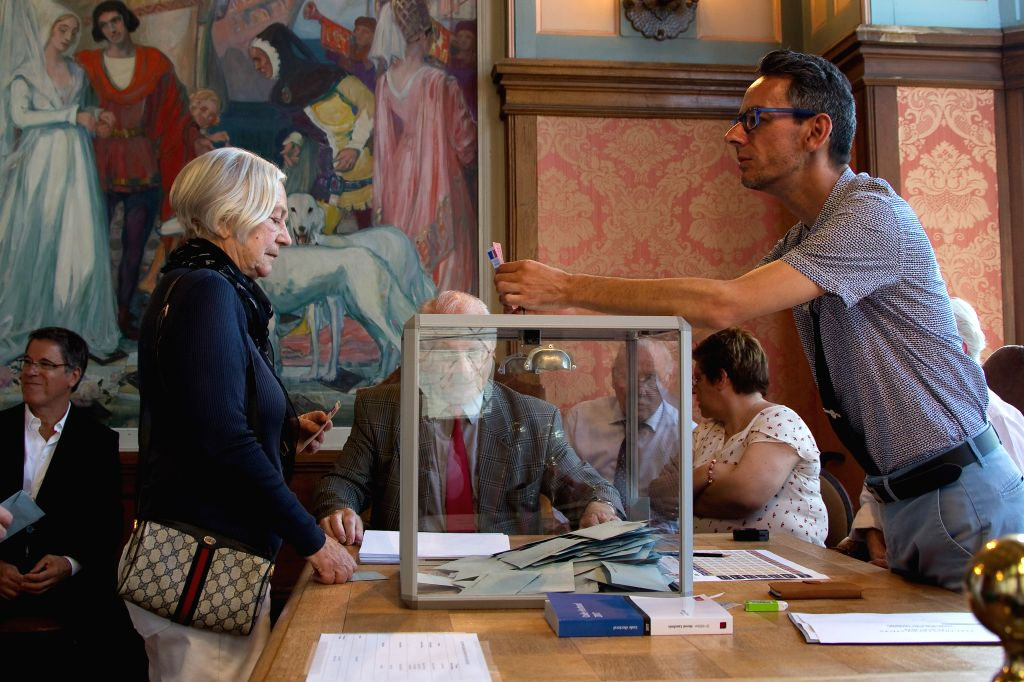 LE BOUQUET, June 18, 2017 - A woman(L) votes during the second round of the parliamentary election at the city hall of Le Touquet, France on June 18, 2017.