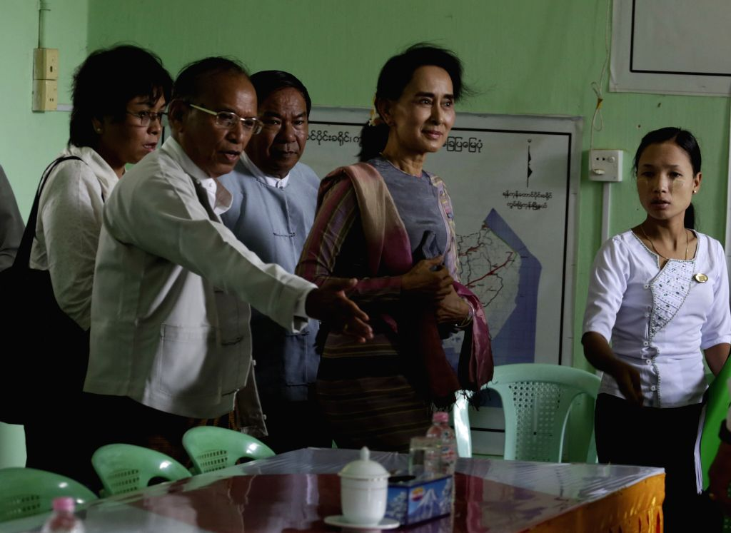 Leader of Myanmar's National League for Democracy (NLD) Aung San Suu Kyi (2nd R) arrives to submit her application for competing at the Kawhmu constituency in the ...