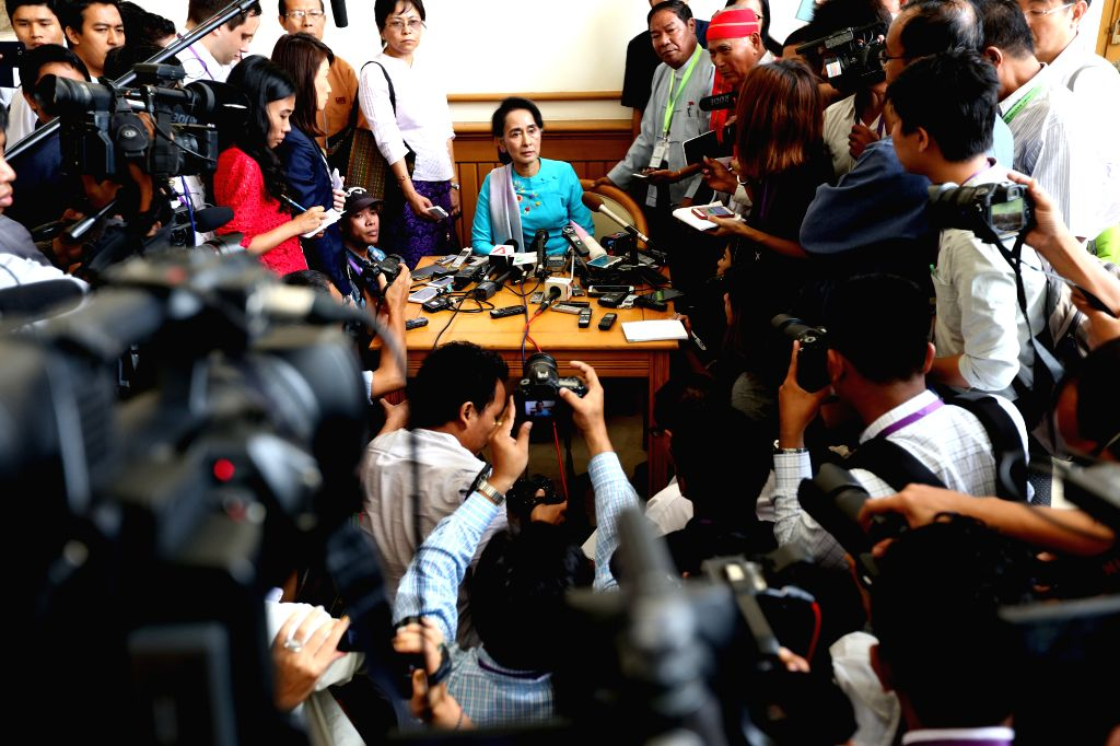 Leader of Myanmar's National League for Democracy (NLD) Aung San Suu Kyi (C) speaks to media at the House of Representatives (Lower House) in Nay Pyi Taw, ...