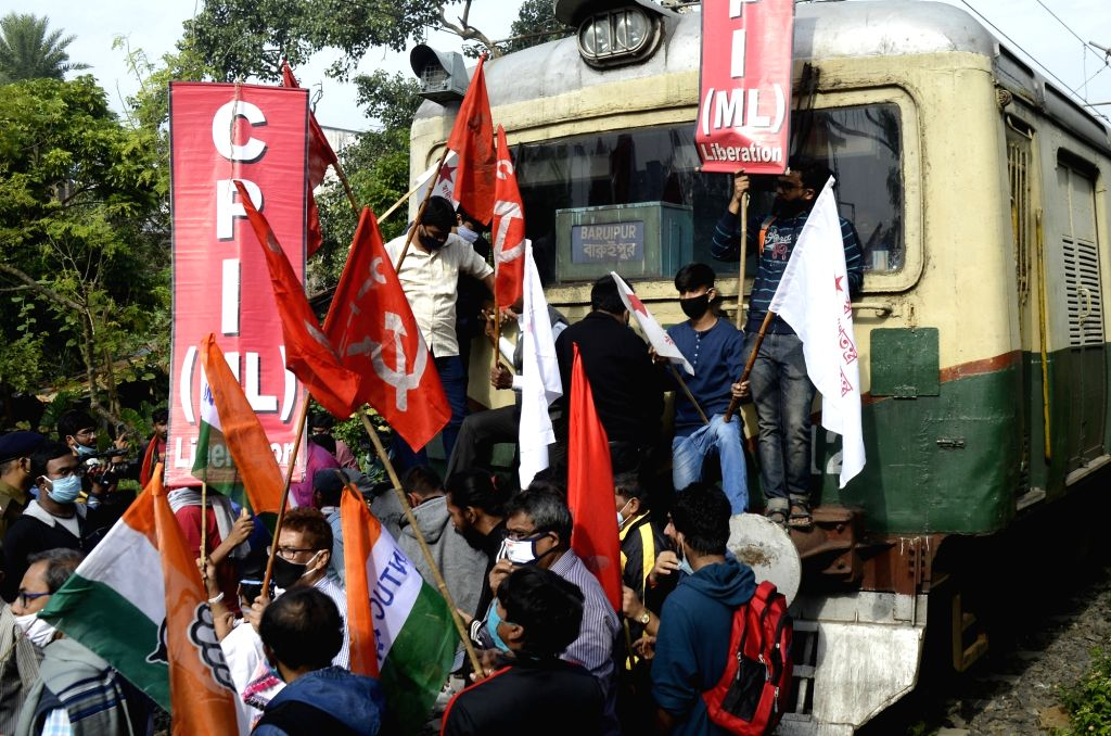 Left and Congress activists block railway tracks as they protest during the 24-hour nationwide trade union strike called by the central trade unions against the central government's new farm ...