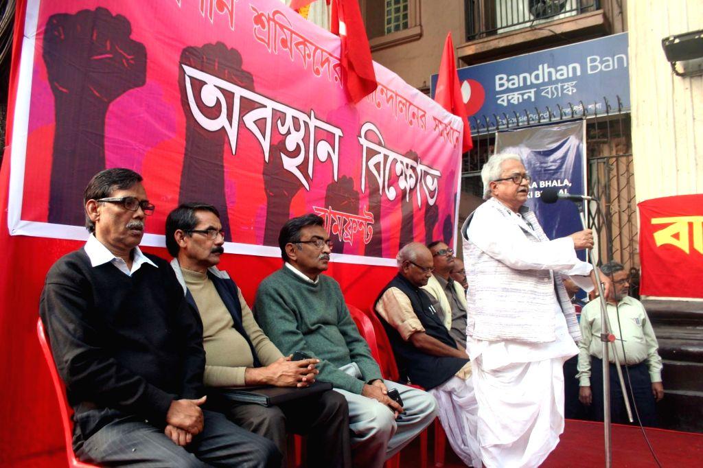 Left Front chairman Biman Bose addresses during a programme organised to support tea garden workers in Kolkata, on Jan 14, 2016. Also seen CPI-M state secretary Surjya Kanta Mishra. - Biman Bose and Surjya Kanta Mishra