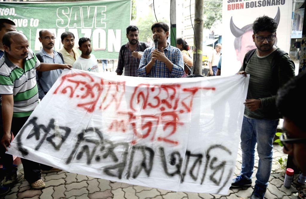 Leftist activists stage a protest against Brazilian President Jair Bolsonaro over Amazon fire; in Kolkata on Aug 27, 2019.
