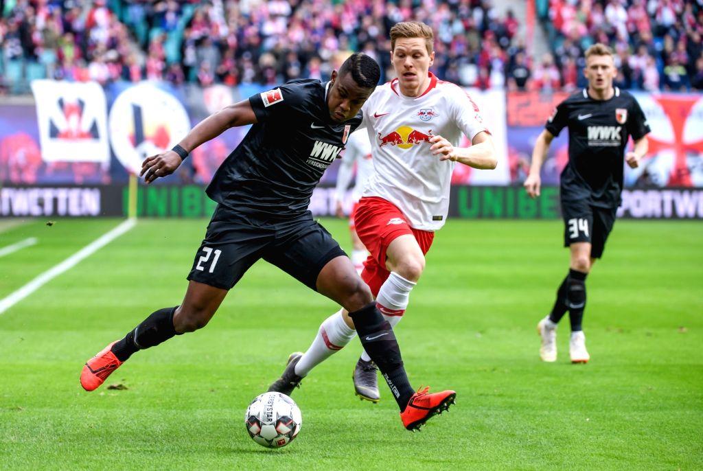 LEIPZIG, March 10, 2019 - Augsburg's Sergio Cordova (L) vies with Leipzig's Marcel Halstenberg (C) during a German Bundesliga match between RB Leipzig and FC Augsburg, in Leipzig, Germany, on March ...